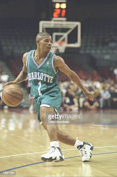 Guard Tyrone Bogues of the Charlotte Hornets dribbles the ball around the perimeter during a game against the Los Angeles Clippers at the Los Angeles...