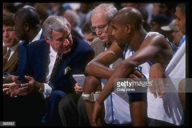 Head coach Dean Smith of the North Carolina Tar Heels confers with guard Vince Carter as assistant coach Bill Guthridge sits in the middle during the...