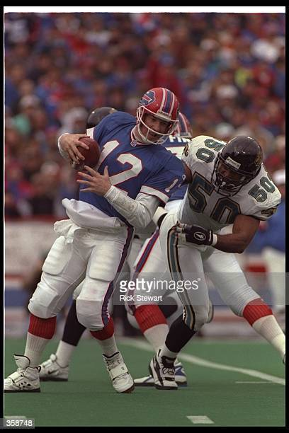 Linebacker Eddie Robinson of the Jacksonville Jaguars tackles Buffalo Bills quarterback Jim Kelly during a playoff game at Rich Stadium in Orchard...