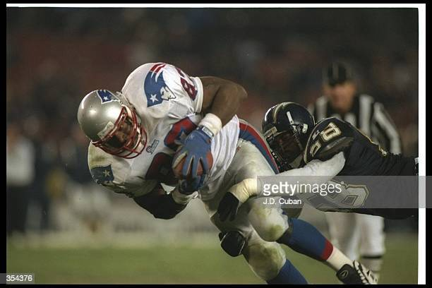 Linebacker Lewis Rush of the San Diego Chargers tackles New England Patriots tight end Ben Coates during a game at Jack Murphy Stadium in San Diego...