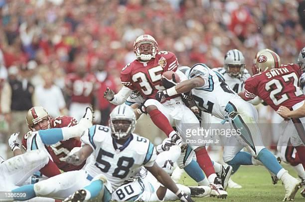 Linebacker Michael Bates of the Carolina Panthers tackles running back Dexter Carter of the San Francisco 49ers at 3Com Park in San Francisco...
