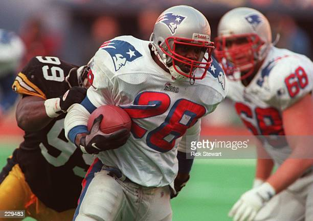 Running back Curtis Martin of the New England Patriots breaks through the tackle of Levon Kirkland of the Pittsburgh Steelers during the Patriots...
