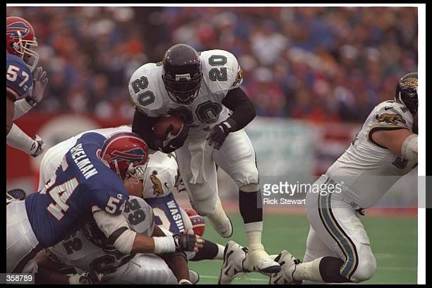 Running back Natrone Means of the Jacksonville Jaguars moves the ball during a playoff game against the Buffalo Bills at Rich Stadium in Orchard...