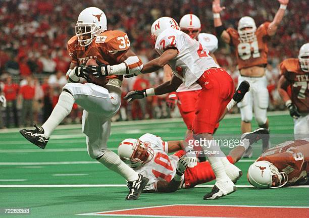 Running Back Priest Holmes of the University of Texas Longhorns high steps into the endzone past Ralph Brown and Mike Minter of the University of...