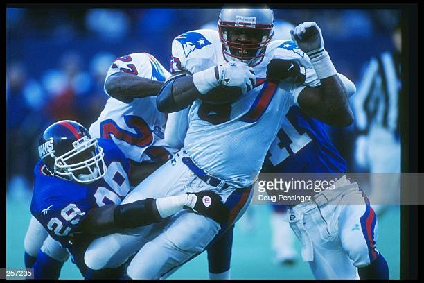 Tight end Ben Coates of the New England Patriots is wrapped up by defensive back Tito Wooten of the Giants during the Patriots 2322 win over the New...