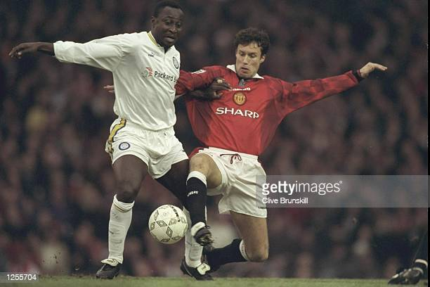 Tony Yeboah of Leeds is challenged by Ronny Johnson of Manchester United during the Premier League match at Old Trafford Manchester Manchester United...