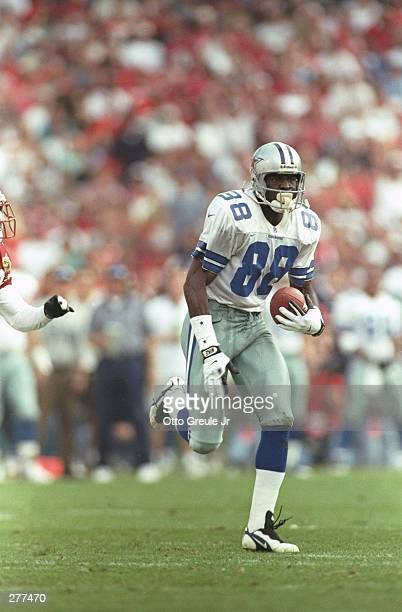 Wide receiver Michael Irvin of the Dallas Cowboys carries the football after making a catch during the Cowboys 106 win over the Arizona Cardinals at...