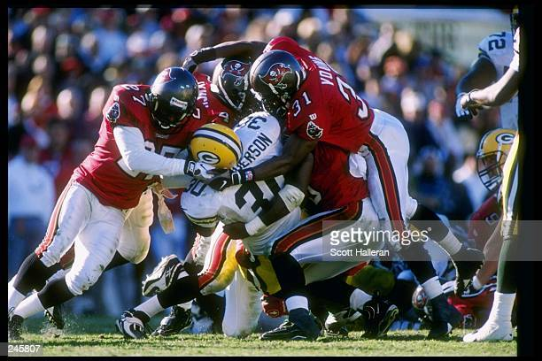 A group of Tampa Bay Buccaneers tackle running back William Henderson of the Green Bay Packers during a game at Houlihan''s Stadium in Tampa Florida...