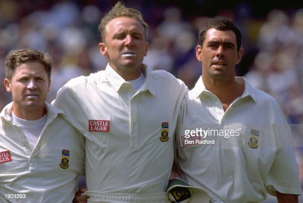 Darryl Cullinan Allan Donald and Hansie Cronje all of South Africa link arms during their national anthem before the first test match against...