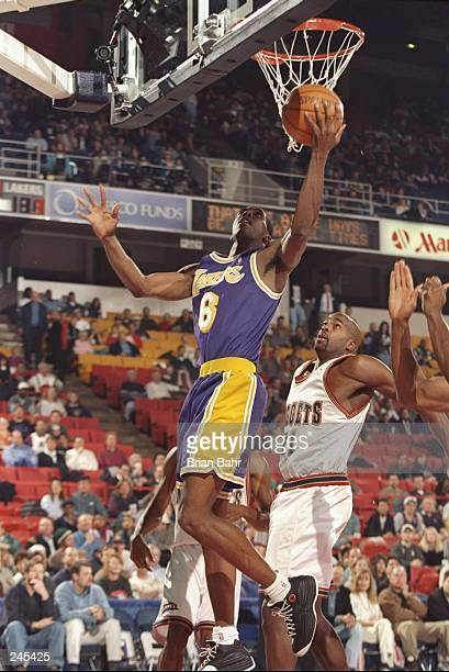 Guard Eddie Jones of the Los Angeles Lakers goes up for two as center Dean Garrett of the Denver Nuggets tries to defend during a game at the...