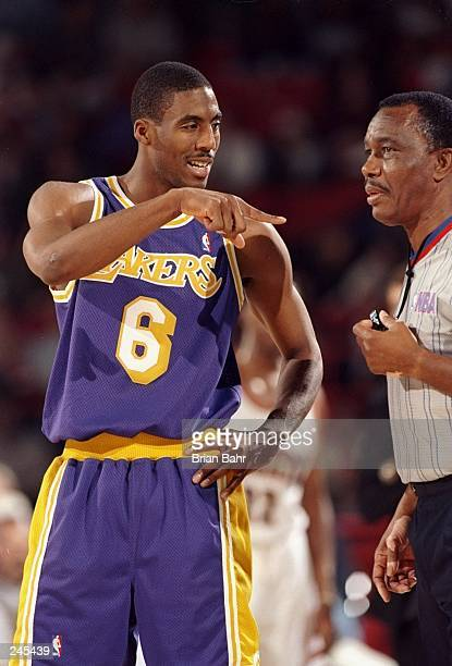 Guard Eddie Jones of the Los Angeles Lakers talks to referee Hue Hollins during a game against the Denver Nuggets at the McNichols Sports Arena in...