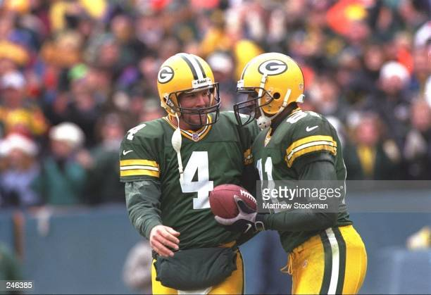 Quarterback Brett Favre of the Green Bay Packers celebrates with teammate Tyrone Davis during the Packers 3121 win over the Buffalo Bills at Lambeau...
