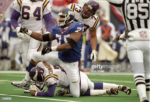 Quarterback Randall Cunningham of the Minnesota Vikings is sacked by defensive tackle Robert Harris of the New York Giants during a game at Giants...