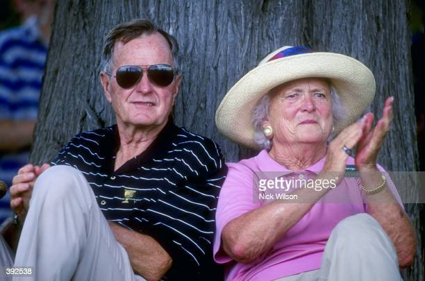 Former United States President George Bush sits by a tree with wife Barbra Bush as they watch the 1998 Presidents Cup at the Royal Melbourne Golf...