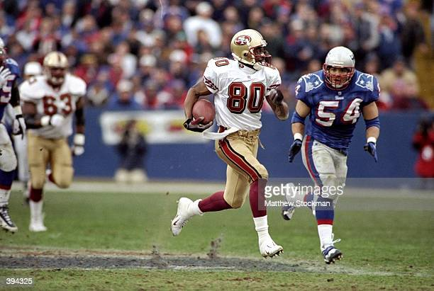 Jerry Rice of the San Francisco 49ers running with the ball being chased by Tedy Bruschi during the game against the New England Patriots at the...