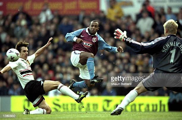 Julian Joachim of Aston Villa beats Gary Neville of Manchester United to get a shot off on Peter Schmeichel during the FA Carling Premiership match...