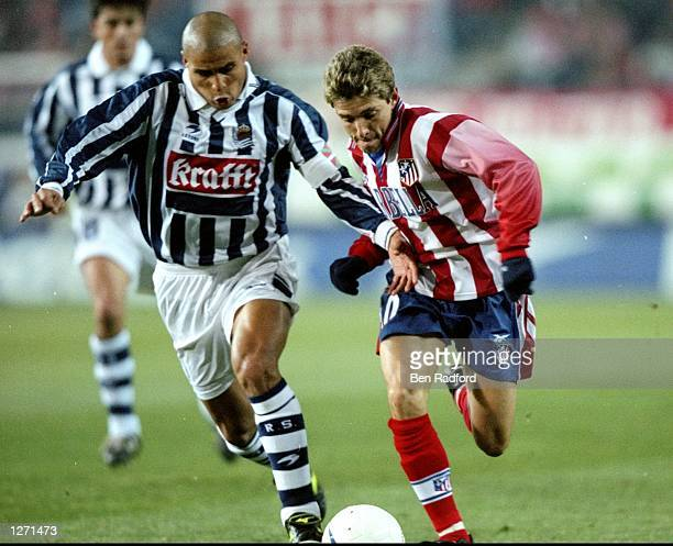 Juninho of Atletico Madrid is challenged by Gomez of Real Sociedad during the UEFA Cup Round 3 Leg 2 match at the Vincente Calderon Stadium in Madrid...