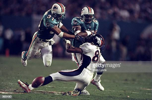 Wide receiver Shannon Sharpe of the Denver Broncos in action against safety Brock Martin and cornerback Patrick Surtain of the Miami Dolphins during...
