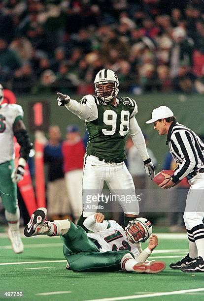 Anthony Pleasant of the New York Jets points from the field as Dan Marino of the Miami Dolphins is on the ground during the game at the Meadowlands...