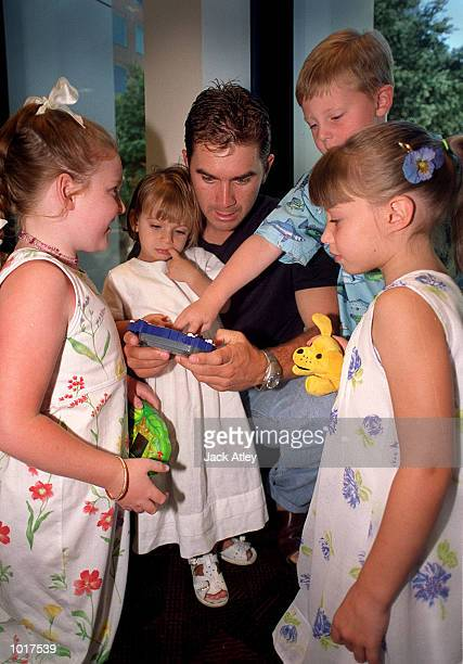 Australian cricket team batsman Justin Langer plays gameboy with daughter Ally Rose and other team members children during the Australian team's...