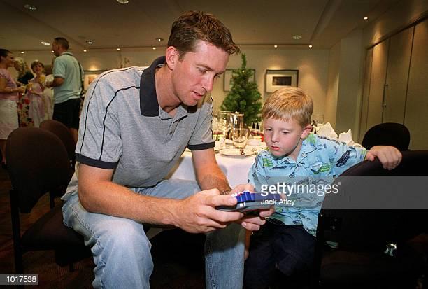 Australian cricket team fast bowler Glenn McGrath plays gameboy with team fitness advisor David Misson's son Conor during the Australian team's...