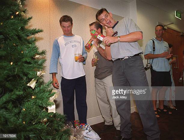 Australian cricketer Adam Gilchrist is elated at his christmas present from fellow players Greg Blewett and Ricky Ponting as team members exchange...
