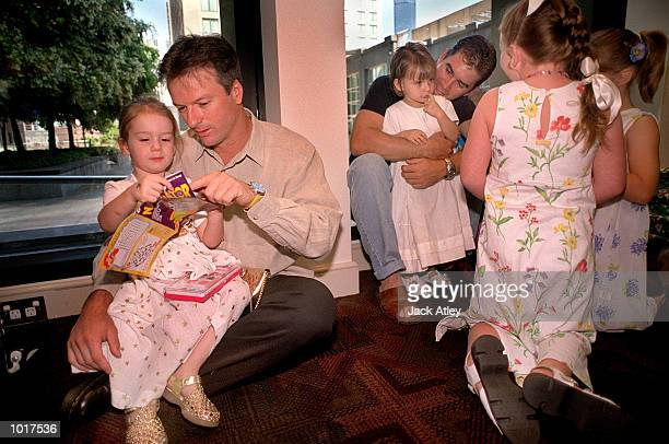 Australian cricketer captain Stephen Waugh watches daughter Rosealie as Justin Langer plays with daughter Ally Rose during the Australian team's...