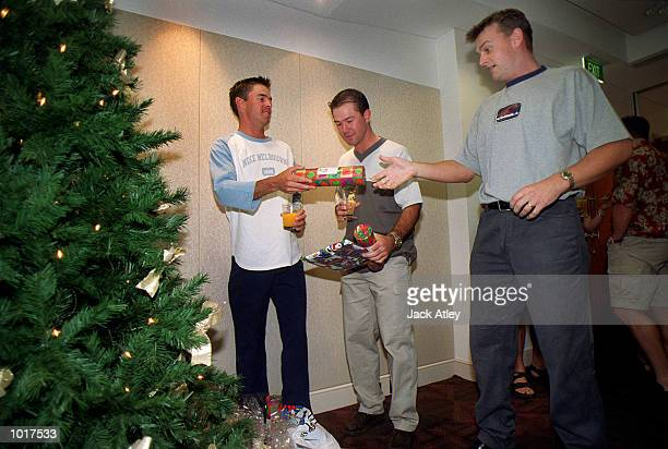 Australian cricketers Greg Blewett Ricky Ponting and Adam Gilchrist exchange presents at the team hotel during their Christmas lunch Tommorrow...