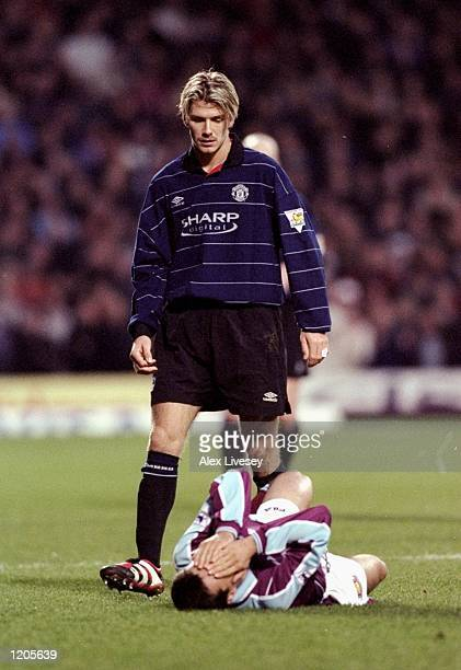 David Beckham of Manchester United looks on as Marc Keller of West Ham United lies injured during the FA Carling Premiership match at Upton Park in...