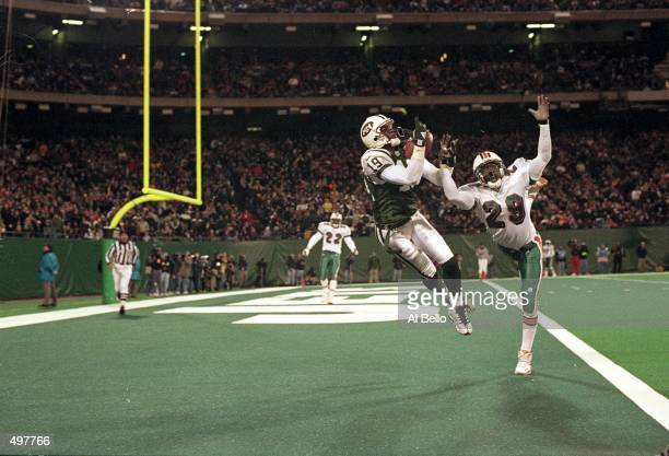 Keyshawn Johnson of the New York Jets catches the ball for a touchdown as Sam Madison of the Miami Dolphins tries to catch it during the game at the...