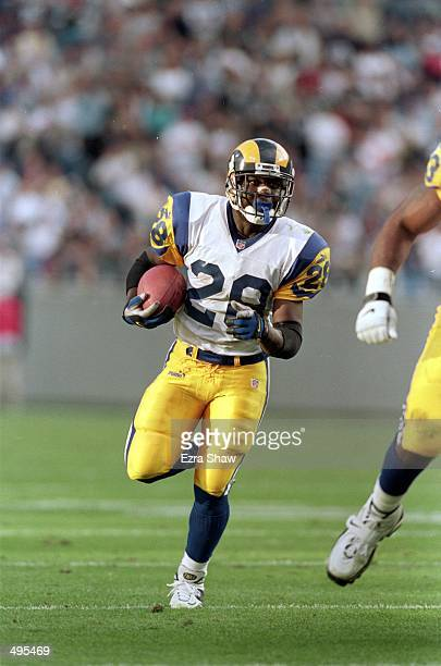 Marshall Faulk of the St Louis Rams carries the ball during a game against the Carolina Panthers at the Ericsson Stadium in Charlotte North Carolina...