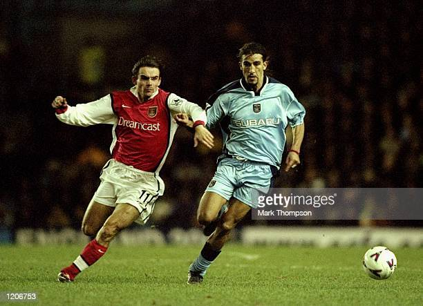Moustapha Hadji of Coventry City holds the ball from Marc Overmars of Arsenal during the FA Carling Premier League match played at Highfield Road in...