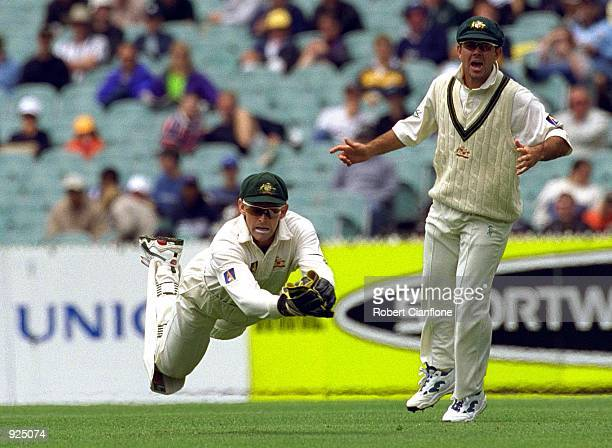 Adam Gilchrist of Australia dives in an attempt to take the catch as Ricky Ponting looks on in the 4th test match between Australia and the West...
