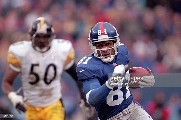 Amani Toomer of the New York Giants runs with the ball against Earl Holmes of the Pittsburgh Steelers during the game at the Giants Stadium in East...