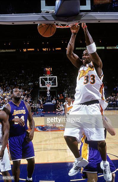 Antawn Jamison of the Golden State Warriors makes a slam dunk as Shaquille O''Nela of the Los Angeles Lakers watches at the Arena in Oakland in...