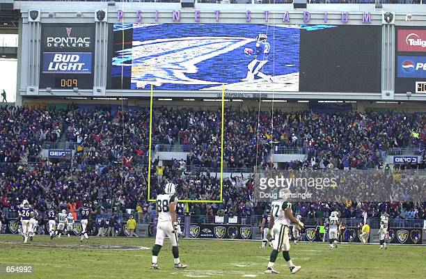 Anthony Becht and Randy Thomas of the New York Jets leave the field and watch the big screen as Chris McAlister of the Baltimore Ravens scores a...