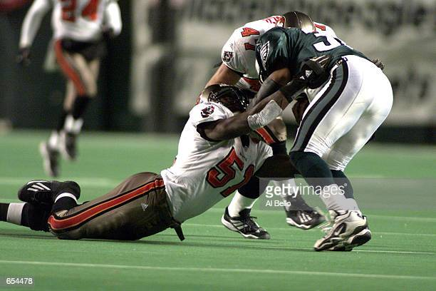 Buccaneers John Lynch and Nate Webster tackle Eagles running back Chris Warren during the NFC Wild Card game between the Tampa Bay Buccaneers and the...