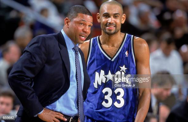 Grant Hill of the Orlando Magic smiles and looks on with Head Coach ''Doc'' Rivers during the game against the Seattle SuperSonics at the Key Arena...