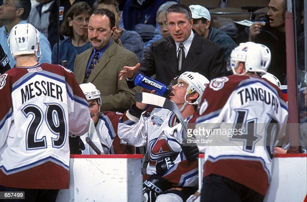 Head Coach Bob Hartley of the Colorado Avalanche hands his player a bottle of water during the game against the Dallas Stars at the Pepsi Center in...