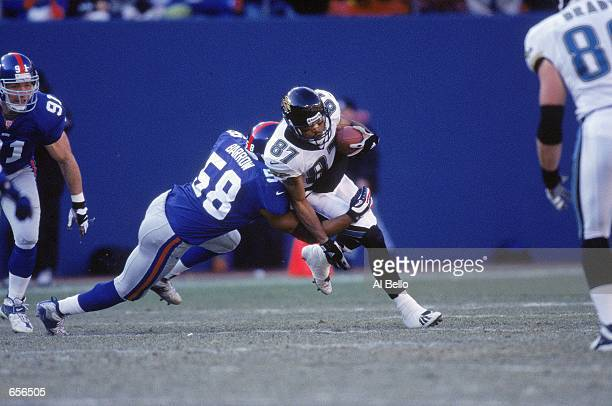 Keenan McCardell of the Jacksonville Jaguars carries the ball as he is tackled by Michael Barrow of the New York Giants at the Giants Stadium in East...