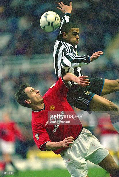 Kieron Dyer of Newcastle United rises above Gary Neville of Manchester United during the FA Carling Premiership match played at St James Park in...