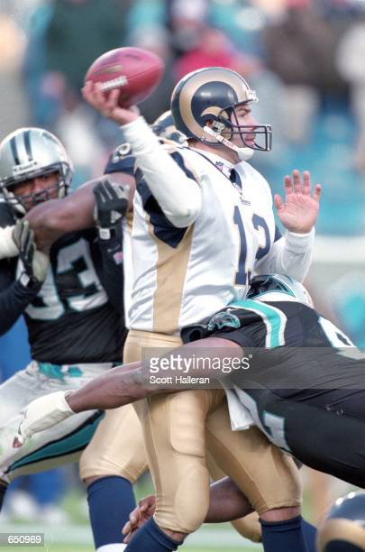 Kurt Warner of the St. Louis Rams passes the ball as he gets tackled by Reggie White of the Carolina Panthers during the game at the Ericsson Stadium...