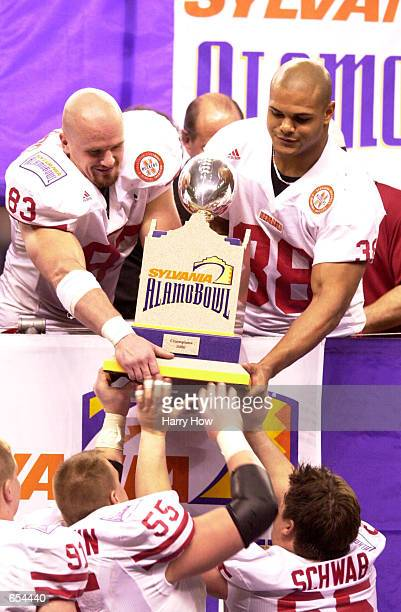 Kyle Vanden Bosch and Dan Alexander of Nebraska pass along the trophy to teammates in celebration of a 6617 win over Northwestern after the Alamo...