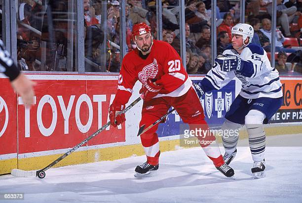 Martin Lapointe of the Detroit Red Wings gets ready to pass the puck as Tomas Kaberle of the Toronto Maple Leafs is behind him during the game at the...