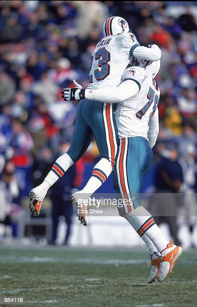 Patrick Surtain of the Miami Dolphins leaps up to hug teammate Kenny Mixon in celebration during the game against the New England Patriots at the...