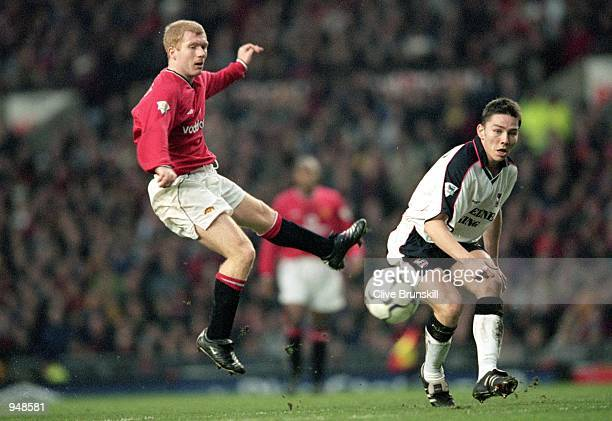 Paul Scholes of Manchester United shoots under pressure from Matt Holland of Ipswich during the FA Carling Premier League match played at Old...