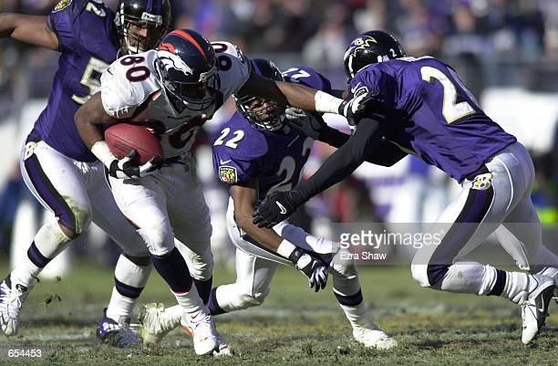 Rod Smith of the Denver Broncos tries to shake off three Baltimore Raven defenders during the AFC Wildcard playoff game at PSINet Stadium in...