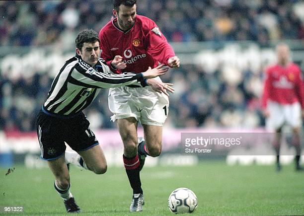 Ryan Giggs of Manchester United charges past Andy Griffin of Newcastle United during the FA Carling Premiership match played at St James Park in...