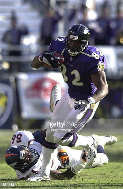 Shannon Sharpe of the Baltimore Ravens eludes a tackle by Al Wilson of the Denver Broncos and runs for a 58-yard touchdown to give the Ravens a 14-3...