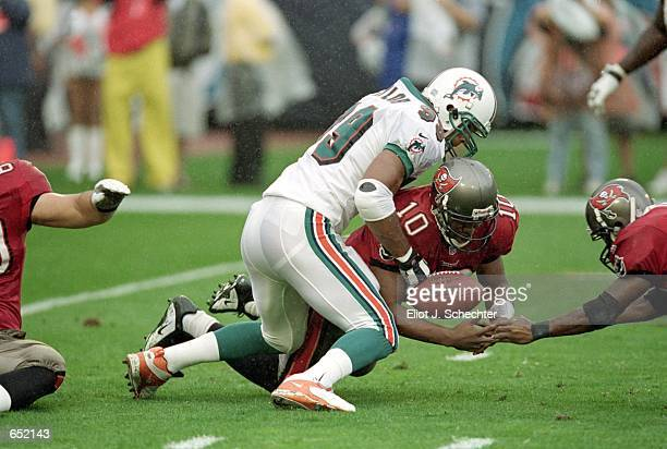 Shaun King of the Tampa Bay Buccaneers igets tackled by Jason Taylor of the Miami Dolphins during the game at the Pro Players Stadium in Miami...